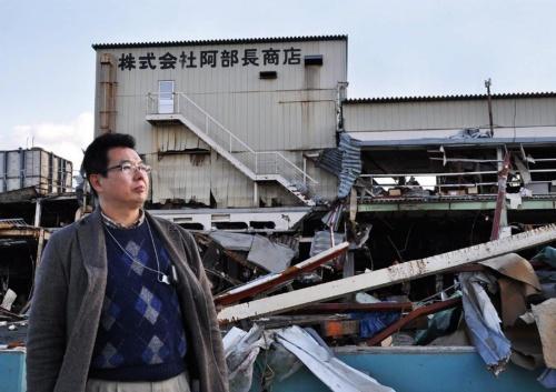 東日本大震災の発生直後、津波で壊滅的な被害を受けた工場前に立つ阿部泰浩社長。自宅も津波に流されていた。