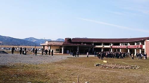 2018年3月11日午後、大川小学校の校舎前で東日本大震災の発生時刻に合わせて黙祷をささげる。年々参列する遺族の数が増えてきているという(筆者撮影)