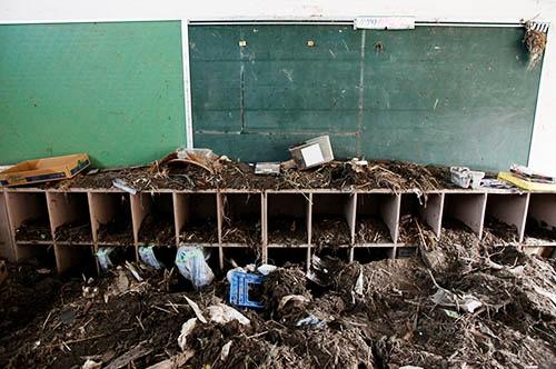 学校全体が大津波にのみこまれ、2階にまで土砂が流れ込んだ。教室や校庭、近隣を覆いつくした土砂やがれきの中から、ランドセルやヘルメットなど大量の生徒の遺品が後日発見されることになった(写真:ロイター/アフロ)