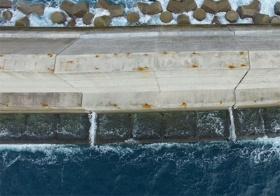 """<span class=""""fontBold"""">沖縄県にある浦添第一防波堤。タイドプールを造ってサンゴの成長を研究している。飛沫が上がるタイドプール間の目地部で、サンゴが育っていることが分かった</span>(写真=港湾空港技術研究所提供)"""