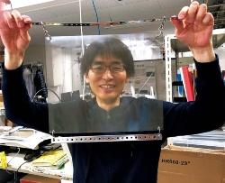 "<span class=""bg_p"">ミュー粒子を検出する乾板を掲げる名古屋大学高等研究院の森島邦博氏</span>"