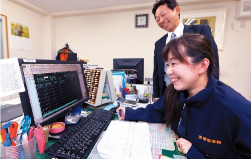 "<span class=""fontBold"">奥澤産業では煩わしい手形の管理業務が減った。負担が減って笑顔の女性社員と奥澤社長</span>(写真=北山 宏一)"