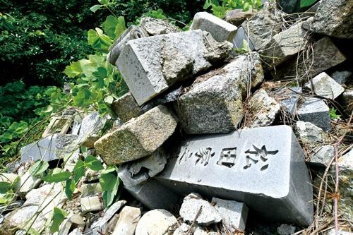 "<span class=""fontBold"">岐阜県の民家の敷地内に乱雑に打ち捨てられた墓石の山。投棄した業者は「代行供養」をうたい、墓じまいの需要を取り込んでいた</span>(写真=早川 俊昭)"