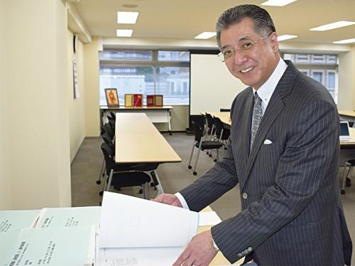 """<span class=""""fontBold"""">マニュアルを手に取る松村氏。「マニュアルにも『カイゼン』の発想を」と語る</span>"""