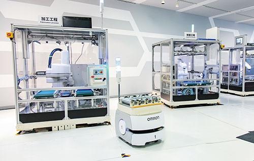 """<span class=""""fontBold"""">オムロン草津事業所の「オートメーションセンタ」では小型ロボットを使った無人製造ラインのデモを披露している</span>(写真=今 紀之)"""