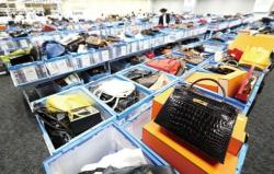 """<span class=""""fontBold"""">オークション会場には高級時計やバッグが大量に陳列してある。バイヤーが事前に商品を触って確認できることが支持につながっている</span>(写真=2点:北山 宏一)"""