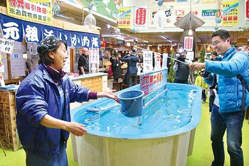<b>イカの街として知られる北海道函館市。写真は水槽から釣り上げたイカをその場で料理する「活いか釣堀」。イカ料理や珍味を提供する飲食店や土産店が市内に数多くある</b>(写真=共同通信)