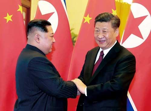 "<span class=""fontBold"">電撃訪中し、中国の習近平国家主席(右)との会談で関係改善をアピールする北朝鮮の金正恩委員長</span>(写真=共同通信)"