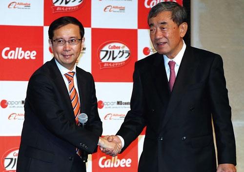 <b>5月25日の記者会見で握手する、カルビーの松本晃会長兼CEO(右)とアリババ集団のダニエル・チャンCEO(左)</b>(写真=つのだよしお/アフロ)