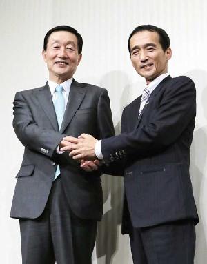 <b>握手を交わすユニーファミマの高柳社長(左)とドンキの大原社長</b>(写真=時事)