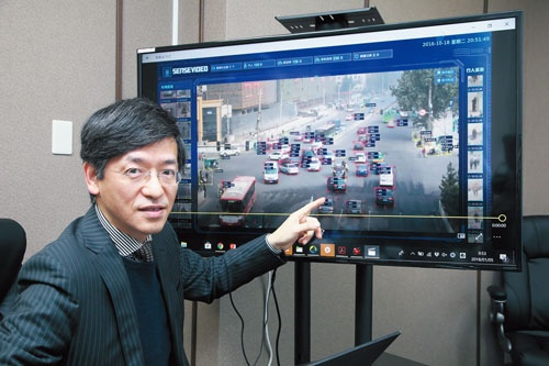 "<span class=""fontBold"">中国・西安の監視カメラ映像を示す、センスタイムジャパンの勞世竑社長。クルマのナンバーや属性を瞬時に把握できる</span>(写真=山田 哲也)"