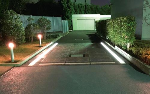 """<span class=""""fontBold"""">道路での発電に向け、NIPPOの総合技術センターの敷地内に太陽光発電モジュールを敷設した。昼間に蓄積した電力で、夜間に周辺の照明やLED照明を用いた区画線をともした</span>(写真=NIPPO提供)"""