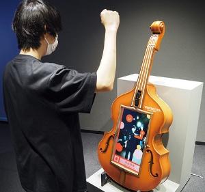 """<span class=""""fontBold"""">バイオリンはガッツポーズで「ド」、少し腕を下げると「レ」など特定の姿勢をとると音が出せる。センサーで肘などの関節点を検出する「姿勢推定技術」を使う</span>"""