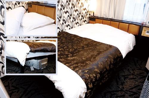 """<span class=""""fontBold"""">1人用の標準客室にも幅140cmのダブルベッドを設置。ベッドは特注品で、身体が沈み込むのが特徴。頭と体の高低差を小さくするため枕はあえて低くする。スーツケースを開けたままベッド下に収納し、引き出しのようにして使うこともできる</span>(写真=竹井 俊晴)"""