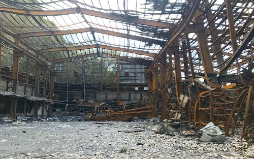 """<span class=""""fontBold"""">沖縄月星は創業70年の節目の年を前に、火災で倉庫や事務所が全焼した。建物の骨組みさえボロボロになってしまった状況に、松本会長は「悔しさばかりが募るが前に進むほかない」と話す</span>"""
