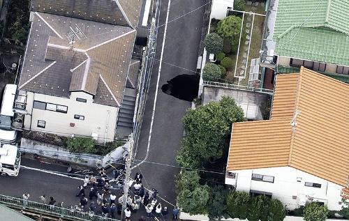 """<span class=""""fontBold"""">東京都調布市の住宅街で2020年10月18日に見つかった道路の陥没現場。地下では外環道のトンネル工事が進んでいた</span>(写真=共同通信)"""