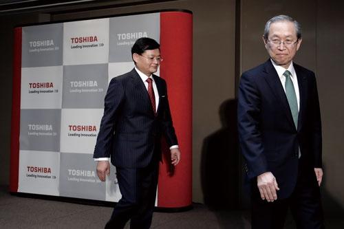 "<span class=""fontBold"">車谷暢昭氏(左)が社長兼CEOを辞任し、綱川智氏が後を継ぐ(写真は2018年2月の経営トップ就任会見)</span>(写真=記者会見:Bloomberg/Getty Images)"