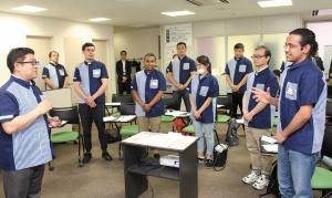 "<span class=""fontBold"">7月にローソンが開いた「外国籍クルー育成講座」。講師の松尾良トレーナー(左端)が業務で使うフレーズを外国籍クルーに教え込んでいた</span>"