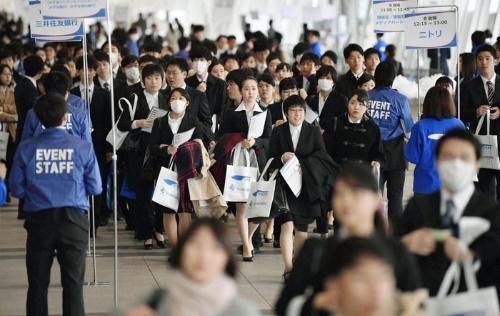 1日、千葉市の幕張メッセで開かれた合同会社説明会の会場に向かう就職活動の学生(写真:共同通信)