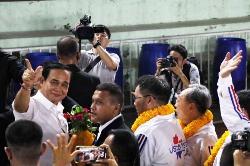 選挙前々日の22日夜、親軍政党が開いた集会に登壇したプラユット暫定首相は去り際、報道陣に対して強気のポーズを見せた(写真左端)