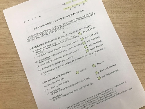 自治体が総務相宛に提出する指定の申出書は、8項目で自治体の担当者がレ点を付ける様式(写真は見本として総務省が自治体向け説明会で渡したもの)