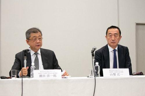 記者会見する潮田氏(左)と山梨広一COO(写真=的野 弘路)