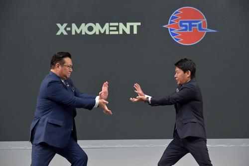 NTTドコモの井伊基之社長(左)とカプコンの辻本春弘社長COO(右)は、互いに向けて「必殺技」を繰り出した。