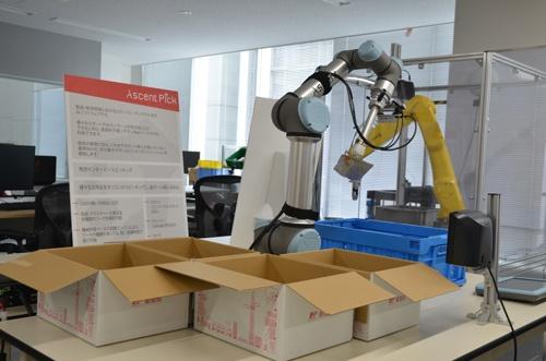 複数の日用品から必要な商品をピッキングして配達用の段ボールに梱包するデモ