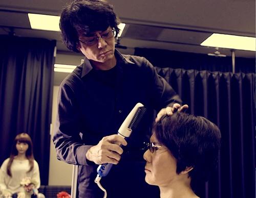 自分そっくりのアンドロイドの身だしなみを整える石黒浩教授(写真:大阪大学)