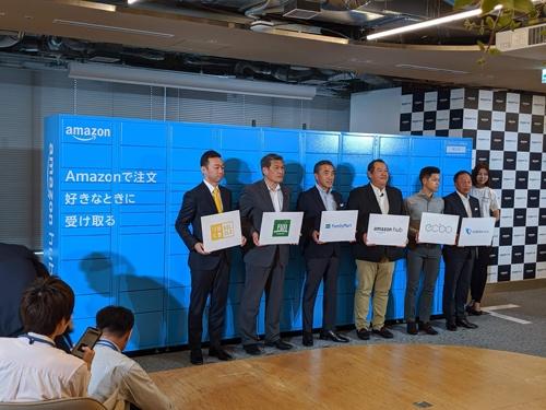 新サービス「Amazon Hub」を発表するアマゾンジャパンのジェフ・ハヤシダ社長(左から4人目)ら