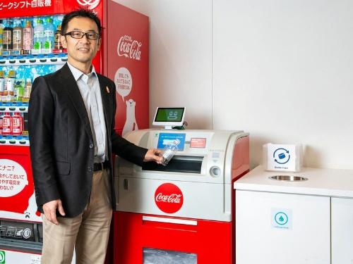 日本コカ・コーラ社内に設置されている綺麗な空容器を回収する「リバースベンディングマシーン(RVM)」。RVMの利用を通じて、社員全員がリサイクルに対する意識をさらに高め、毎日の行動に落とし込んでもらう狙いだ。(写真人物)日本コカ・コーラ 環境サステナビリティーガバナンス部長 柴田 充 氏