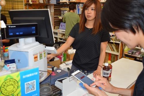 スマートフォンにさるぼぼコインをチャージして使用する。支払いのときは、レジ横にあるQRコードを読み込む