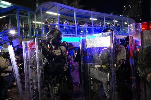警官たちが防毒マスクを装着した。デモ隊も催涙弾に備え始める。(写真以下3点/的野弘路)