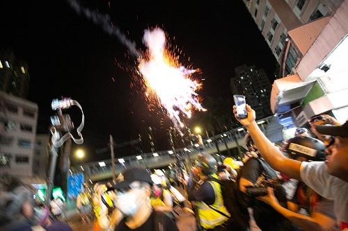 警告後に催涙弾が放たれた。火花が散り、煙が立ち込める。