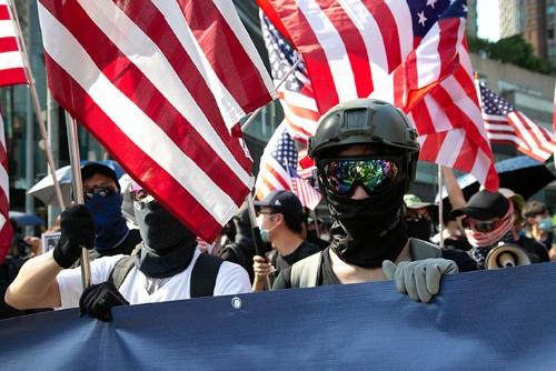催涙弾を警戒して防毒マスクをかぶったデモ参加者が米国に助けを求めている