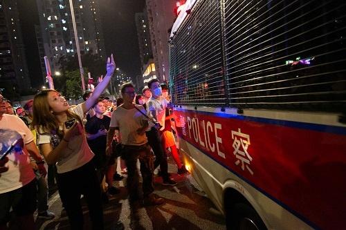 警察車両の後方で、男性が棒で殴りつけようとしている。女性は中指を立てて罵声を浴びせ、車両を蹴り上げていた(写真以下2点/的野弘路)