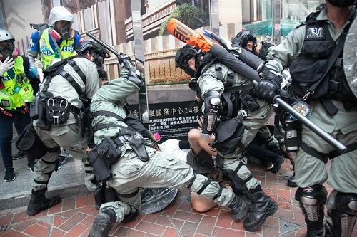 デモ参加者を警棒で殴打し、拘束を試みる警官たち。腰間には拘束具や催涙スプレーに加えて一丁の拳銃を備えている(写真/的野弘路)