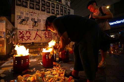 """揺れる炎の前にひざまずいて""""死者""""を悼む人たちが引きも切らなかった(写真以下2点/的野弘路)"""