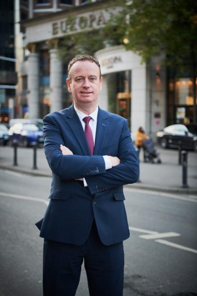マニュファクチャリングNIのステファン・ケリー代表。背景にあるのは、紛争時には欧州で最も爆弾テロがあったベルファストのヨーロッパ・ホテル(写真:永川智子)