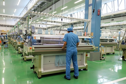 立体的に編み上げて製造するホールガーメント横編機は糸や繊維の無駄が出ない。新型コロナ感染症が拡大する中、小型のホールガーメント横編機を使って多くのマスクがつくられている(写真提供=島精機製作所)
