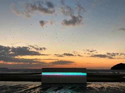 脇田氏の作品「Triplet」。脇田氏のサイトの説明には「生物学におけるTripletと呼ばれる遺伝子暗号の単位に着目し、都市、生物、音楽、映像、社会現象などを対象に、この暗号概念の拡張を試みるプロジェクト」とある。海の中に10メートルのスクリーンを設置し、砂浜から海に向けて映像とサウンドで作品を構成した( 制作協力 8K映像:アストロデザイン 株式会社,技術:株式会社 曽根土木建設)
