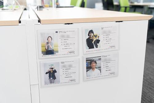 フリーアドレスのデスクの脇に、各部署のメンバーの趣味やモットー、誕生日などを書いたシートを貼っている。これはコロナ前から(写真:稲垣純也)