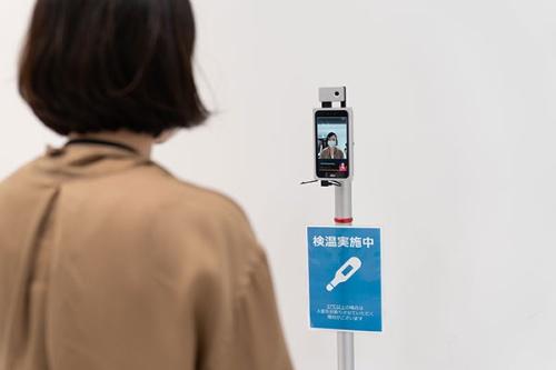 オフィスに入る前に、非接触のシステムで検温(写真:稲垣純也)