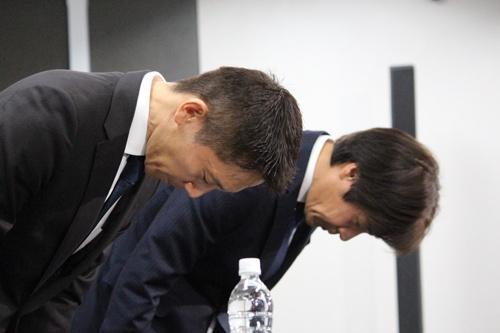 内定辞退率の問題を受け8月に開かれた記者会見で頭を下げるリクルートキャリアの小林大三社長(左・手前)と浅野和之執行役員(右・奥)