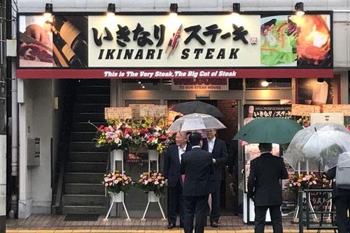 本社(東京・墨田)のそばにオープンした店舗を訪れた一瀬邦夫社長(左)。あいにくの雨に、幹部がすかさず傘を差し出す