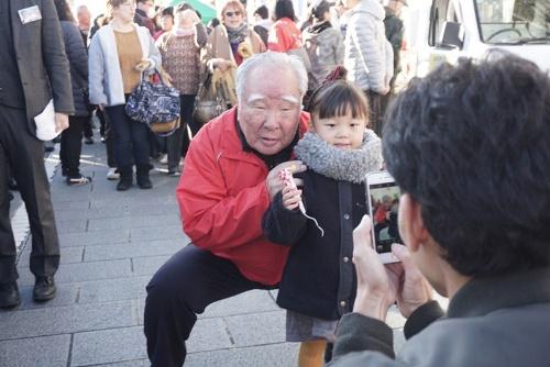 2019年12月に静岡県掛川市で開かれた、軽トラックの荷台で特産品や菓子などを販売する「軽トラ市」で、鈴木修会長は訪れた人から写真や握手を度々求められていた