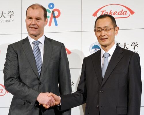 2015年、提携を発表した記者会見後に握手する京都大の山中伸弥教授(右)と武田薬品工業のクリストフ・ウェバー社長(写真:共同通信)