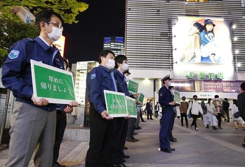 JR新宿駅前で外出自粛などを呼び掛ける都や区の職員ら(写真:共同通信)