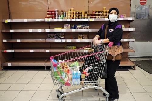 マレーシア政府は18日から全土を封鎖すると発表した。パニックのような買い占めは起きていないようだが、一部の小売店では品不足が顕在化している(写真:ロイター/アフロ)
