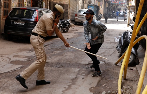 全土を封鎖しているインドで、不要不急の外出をしていると見られる人を打つ警察官(写真:ロイター/アフロ)